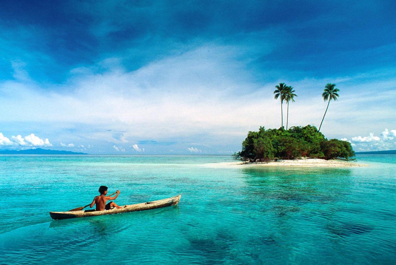Пара на лодке плывет к острову